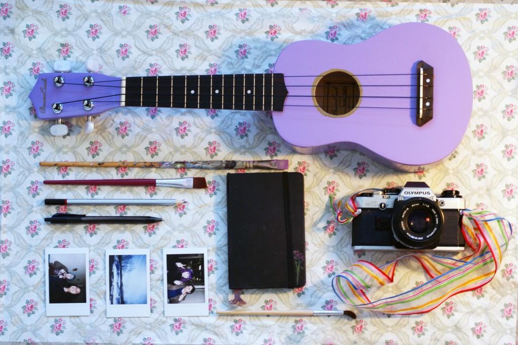photo of: ukulele, journal, camera, paint brushes, and polaroids