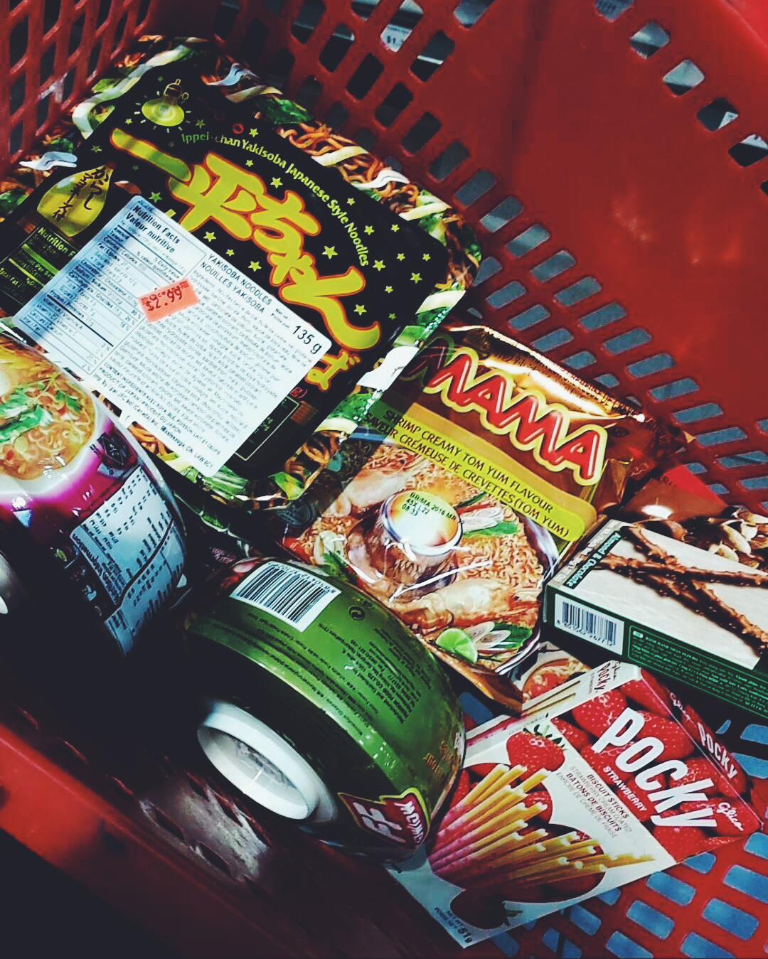 Grocery basket full of instant noodle packages and various snacks.