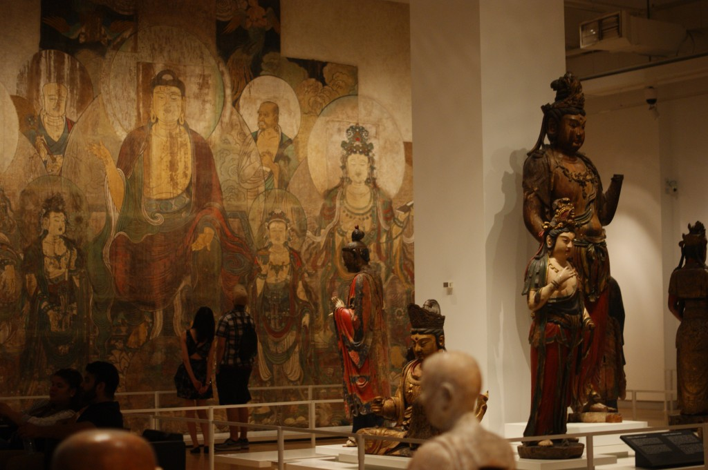 photo of ancient asian temple art, featuring a giant mural of buddha and many statues