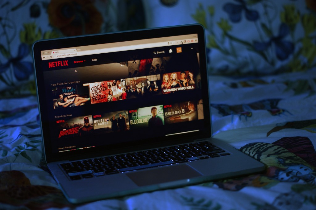 photo of dark bedroom with laptop on bed, netflix is open on the laptop