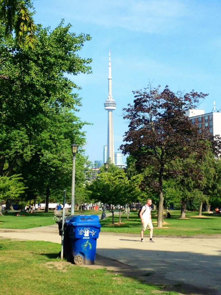 unsightly blue trash can ruining my shot of the CN Tower peeking out from behind trees