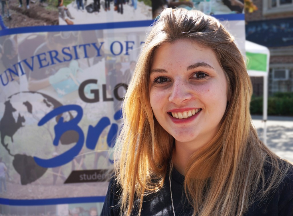 Photo of Rosalyn in front of a U of T Global Brigades banner