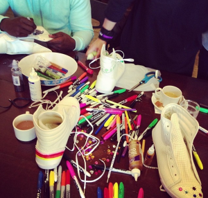 photo of table strewn with markers and plain white sneakers waiting to be decorated