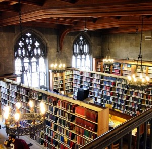 view looking down from second floor of emannuel library- stacks of books and gothic chandeliers and wooden beams