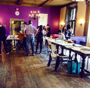 photo of reading room while the crafting is in session- purple wall and people sitting and working at the long table