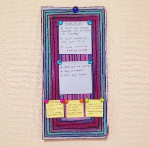 photo of the corkboard pinned up onto my wall and lovingly adorned with pushpins and tiny post-its