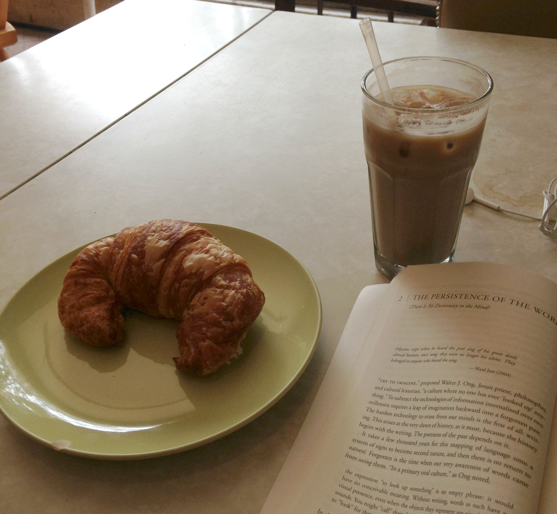 A croissant on a green plate with an iced coffee and an open book in a cafe.
