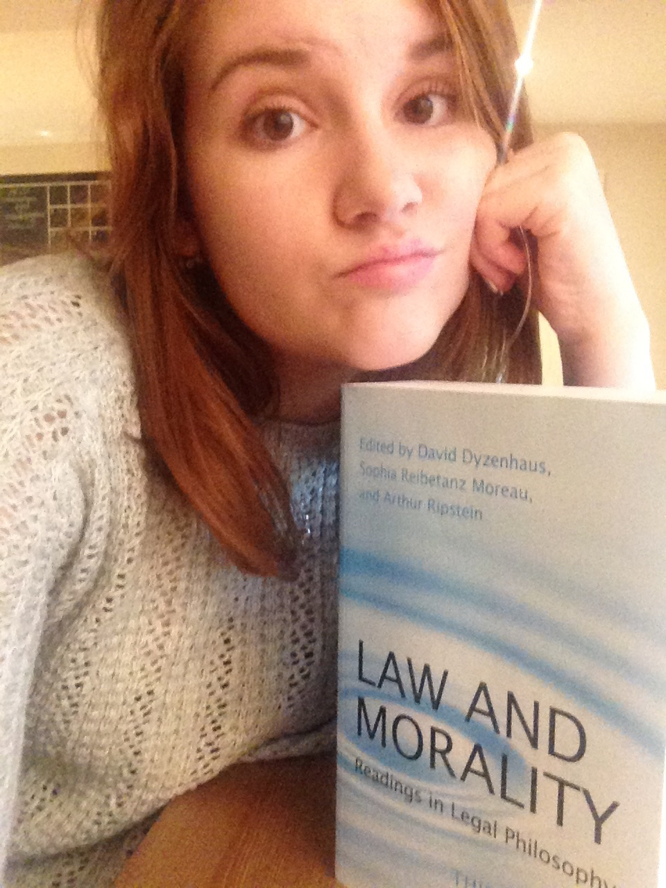Madeline making a grumpy face next to a textbook.