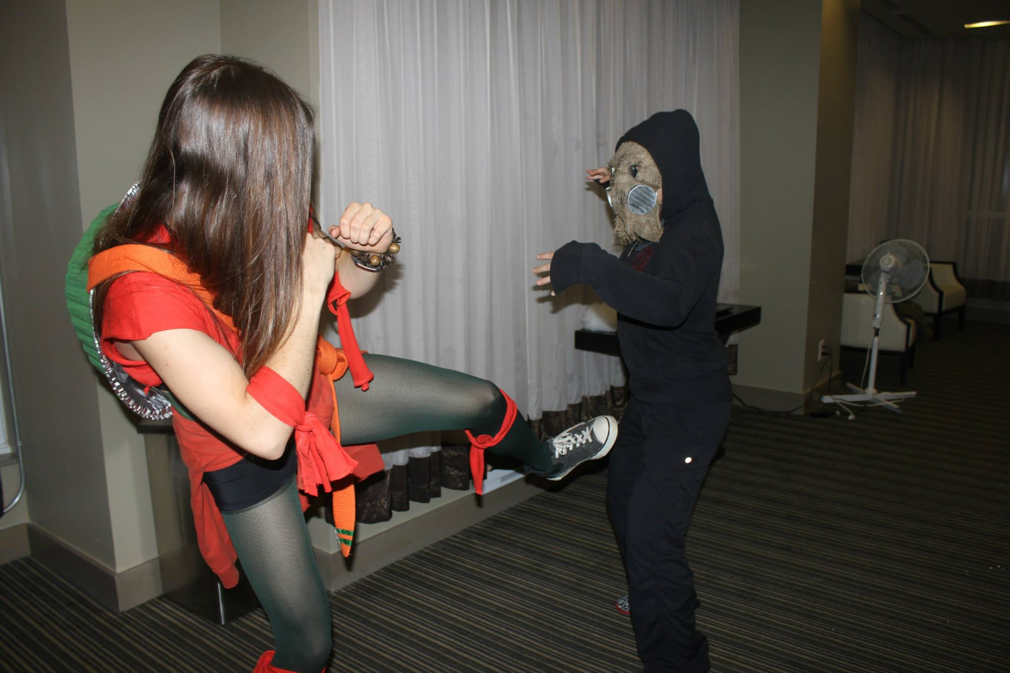 Girl in ninja turtle costume feigning a kick at someone dressed up in all black with a gas a mask -also in fighting stance.