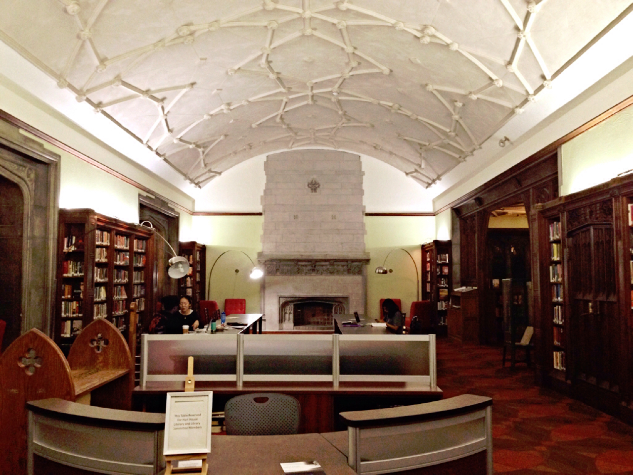 A photograph of Hart House Library; with a cathedral ceiling and wall to wall bookshelves.