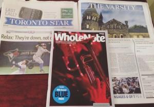 Toronto Star newspaper, The Varsity newspaper, and the Whole Note magazine strewn across my desk.