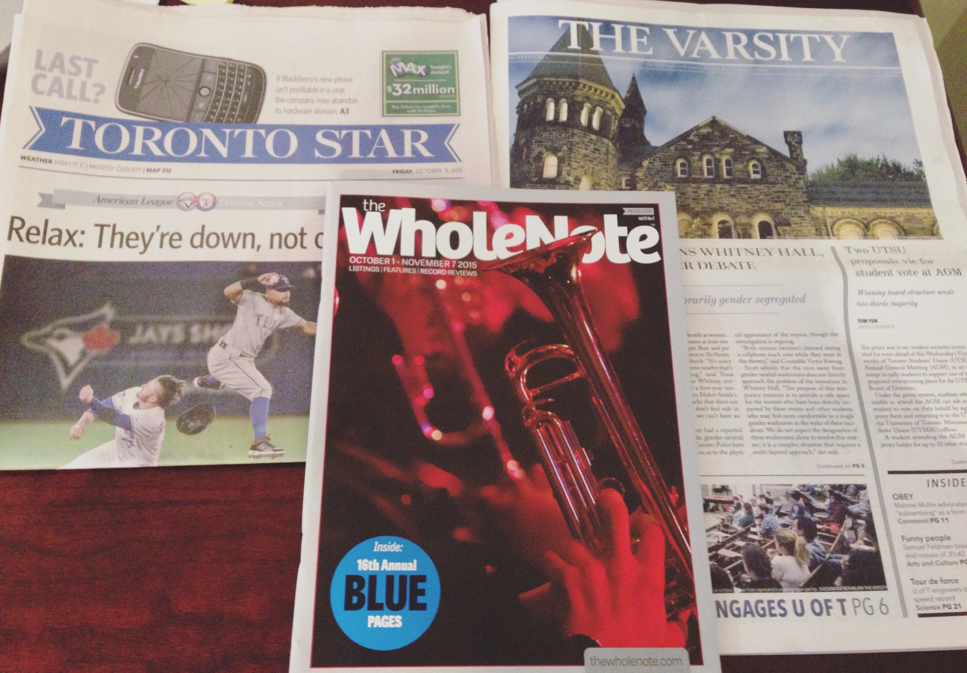 Toronto Star newspaper, The Varsity newspaper, and the Whole Note magazine strewn across my desk.