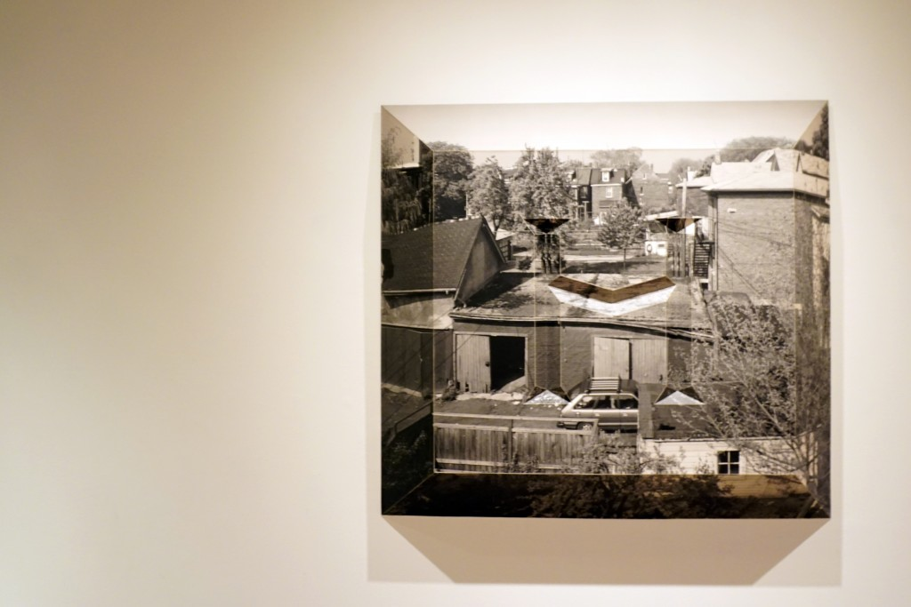 "a photo of backyards in Toronto, shaped into a tombstone like shape with an embossed ""H"""