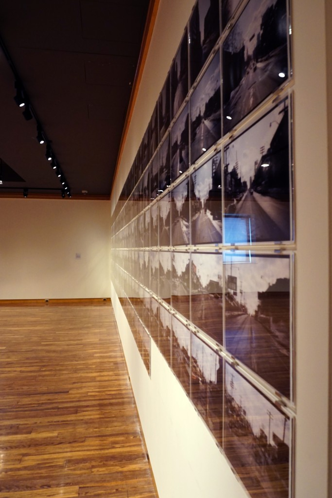 photo of a long wall covered with almost 200 8 x 11 inch photographs