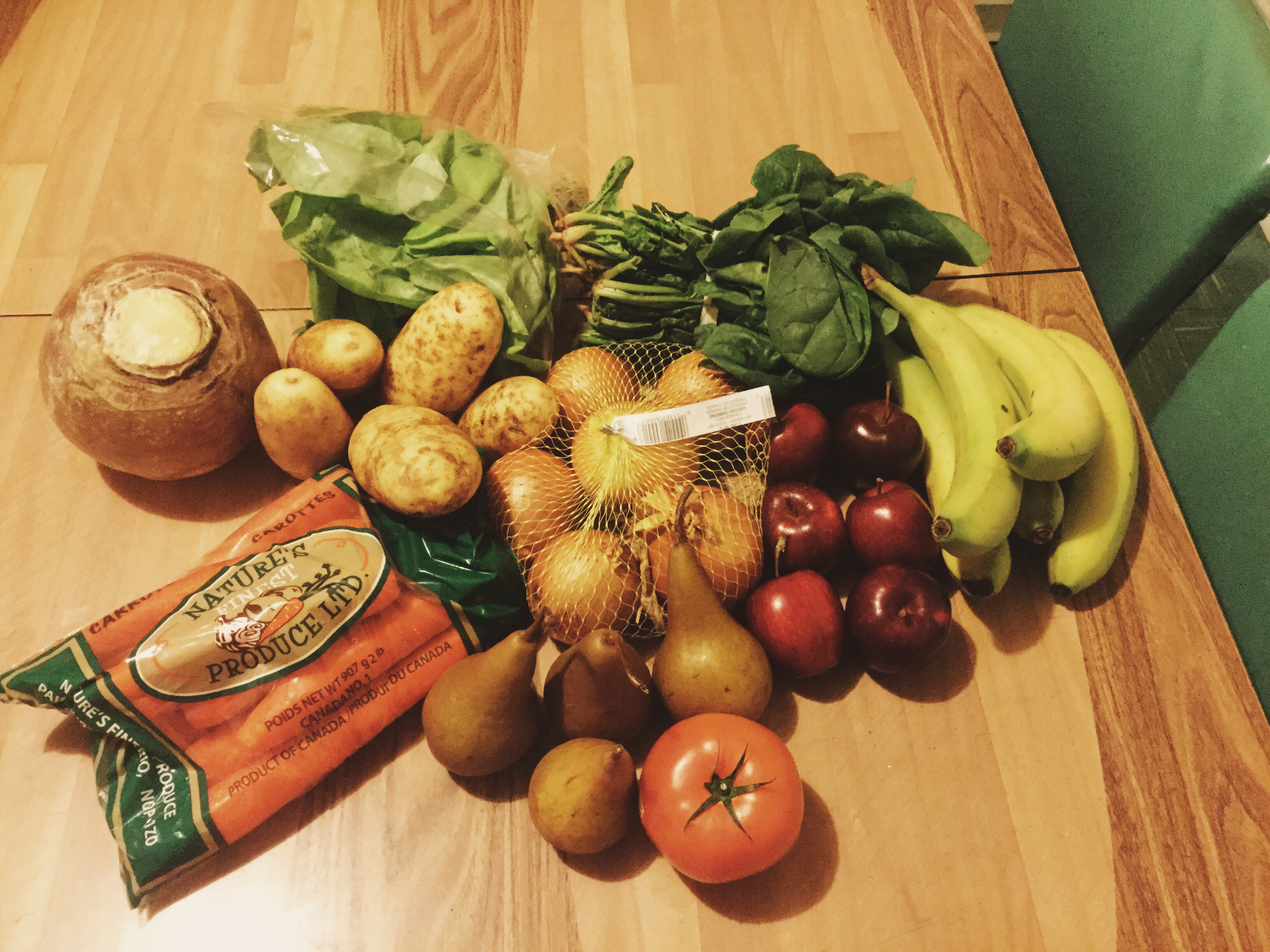 A selection of fresh produce on my dining table including a bag of carrots, potatos, bananas, pears, applies, spinach, lettuce, a bag of onions, and a singular tomato.