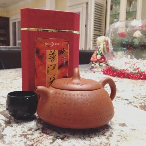 Chinese tea package, cup, and pot.