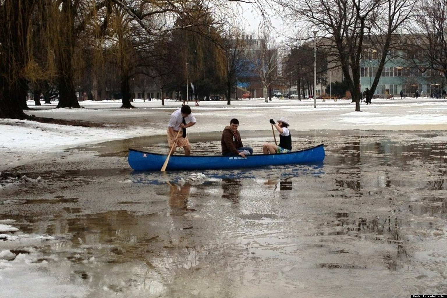 Three students paddling a canoe across a flooded over part of McMaster campus.