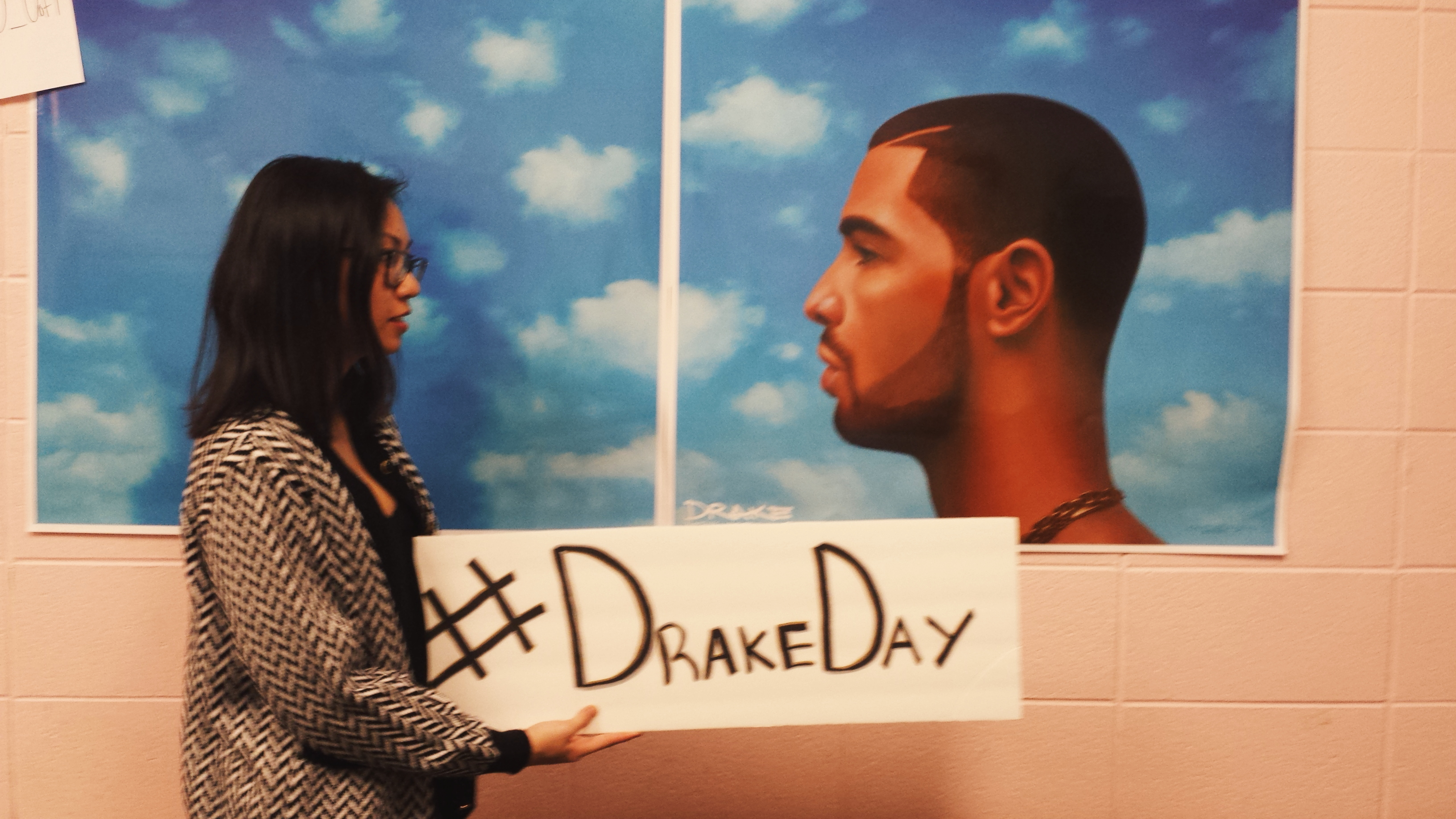 "Me posing with a sign that says ""Drake Day"" in front of a Drake poster."