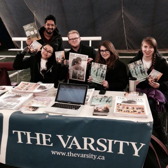 Representatives from The Varsity at a table in Varsity dome holding copies of The Varsity newspaper and magazine at a registration table covered in newspaper issues and a laptop with an open sign-up form.