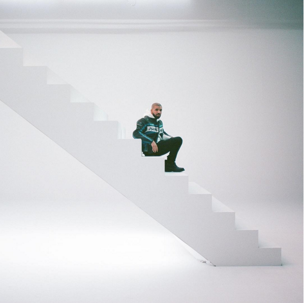 Drake sitting on a white staircase.