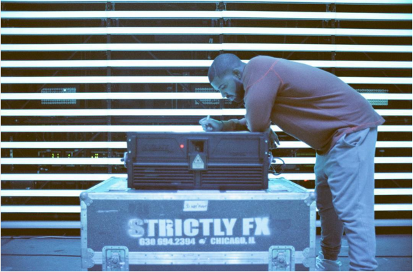 Drake leaning against a large storage container and a stereo, using the stereo as a desk to write lyrics on a piece of paper.