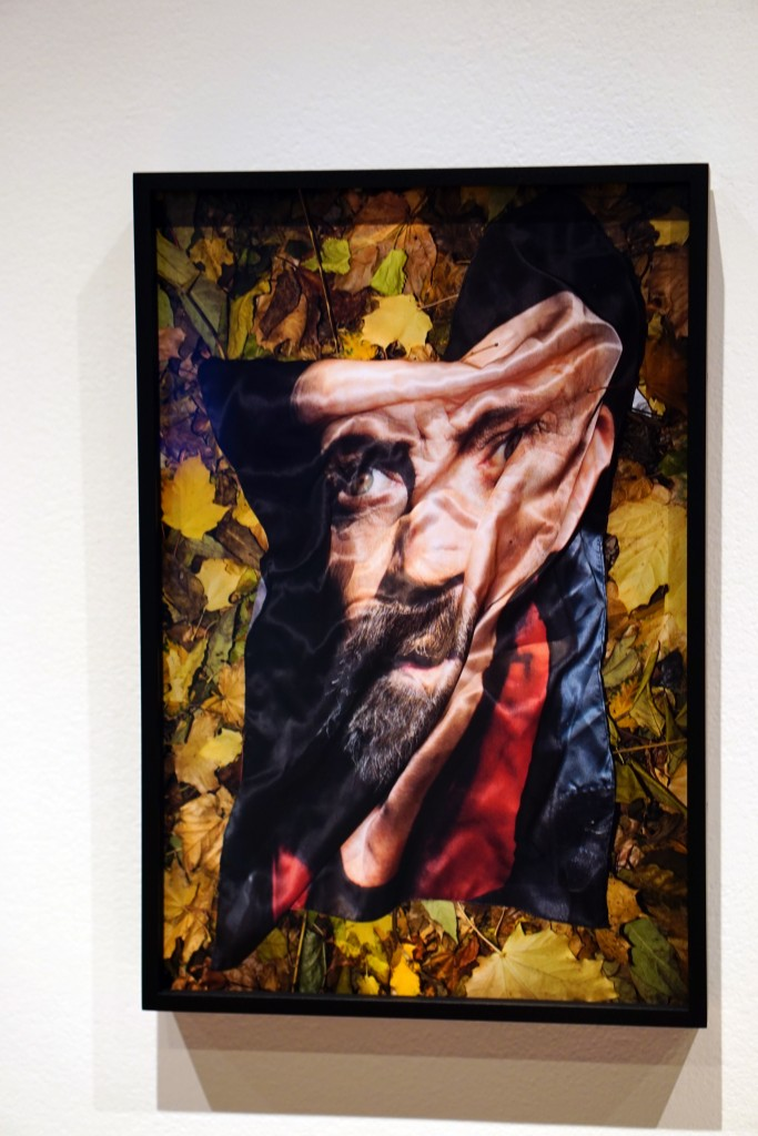 a picture of a portrait on a man printed onto silk fabric that's been left on the ground