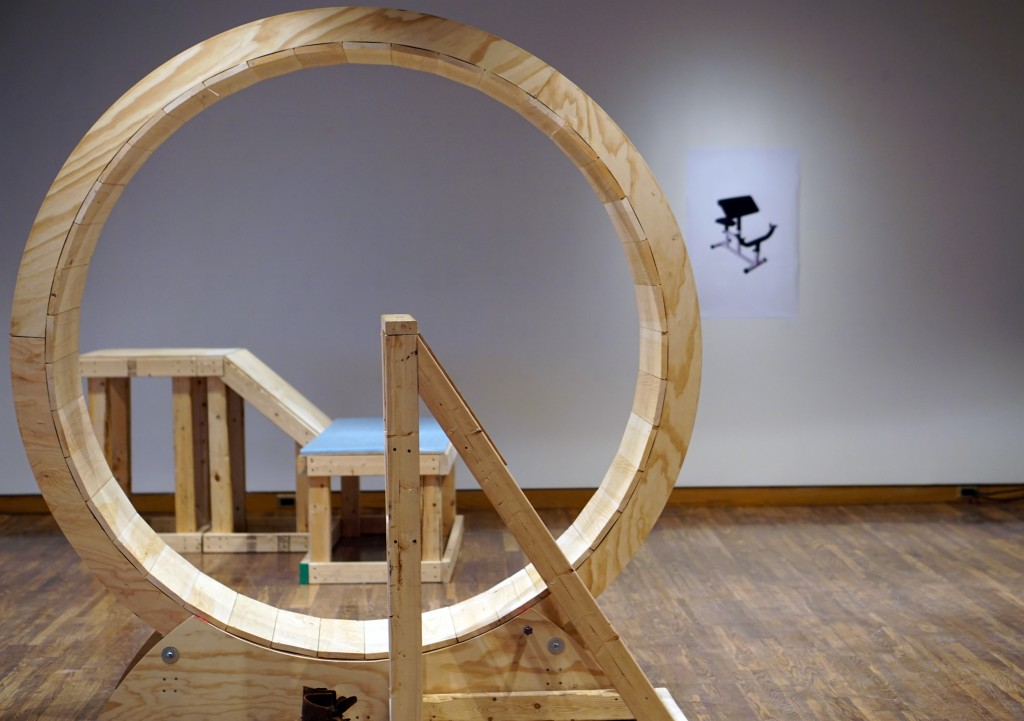 a sculpture that looks like a giant wooden hamster wheel