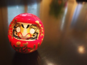 A small Daruma doll on a table.