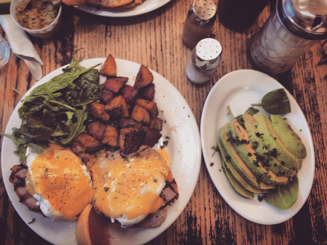 A photo of eggs benedict with home fries and arugula salad.