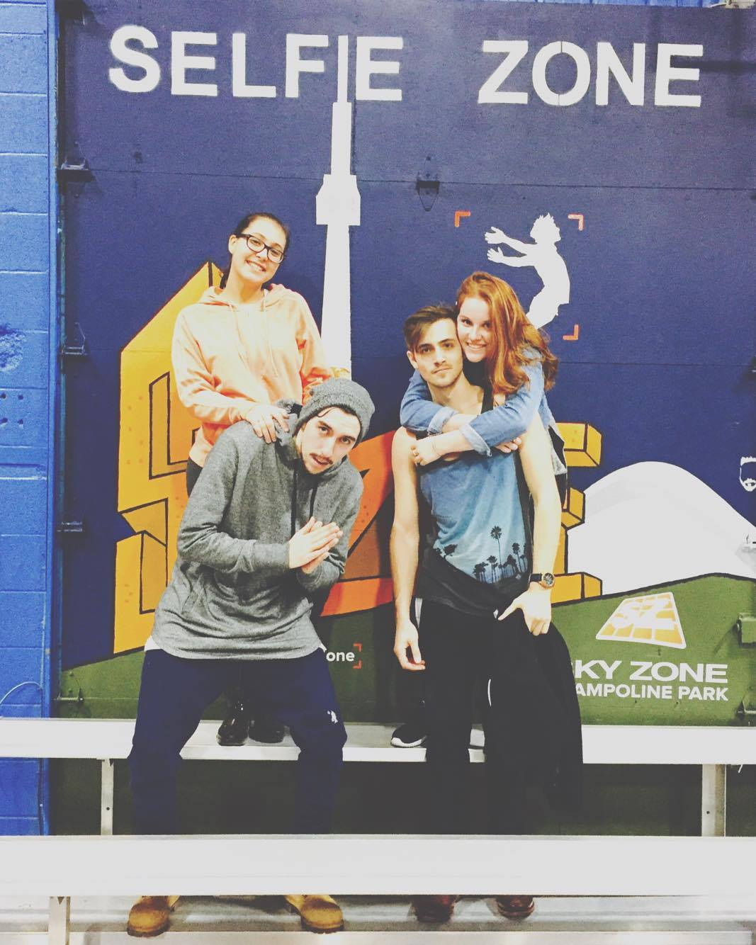 Madeline and 3 friends posing on a bench with a toronto themed background to commemorate the trampoline experience.