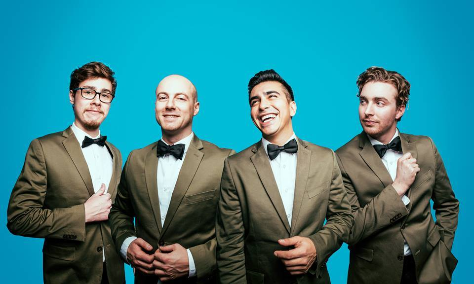 A photo of the Dreamboats (4 young men) in suits posing for a picture.