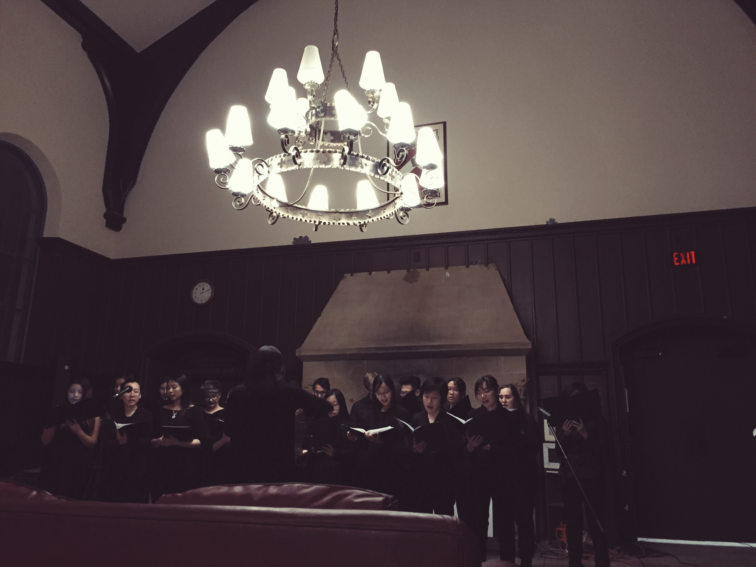 The group of students from Innis Choir performing in the JCR. A conductor helps keep the singers in sync.