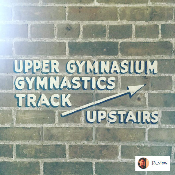 A painted sign that directs you upstairs to the gymnasium track in Hart House gym.