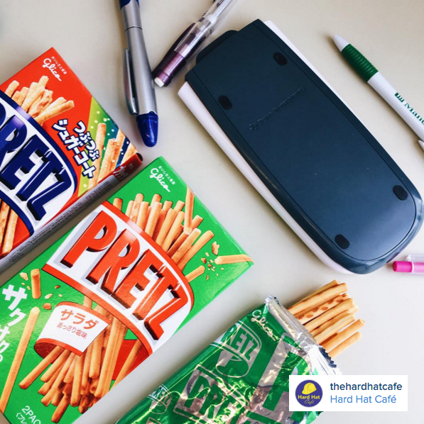 Colourful boxes of Pretzals beside pens and a calculator on a desk.