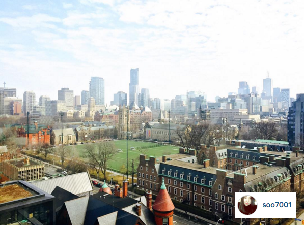 A scene of back campus as seen from the Robarts Stacks. The back field, Whitney Hall, and the Toronto horizon can be seen.