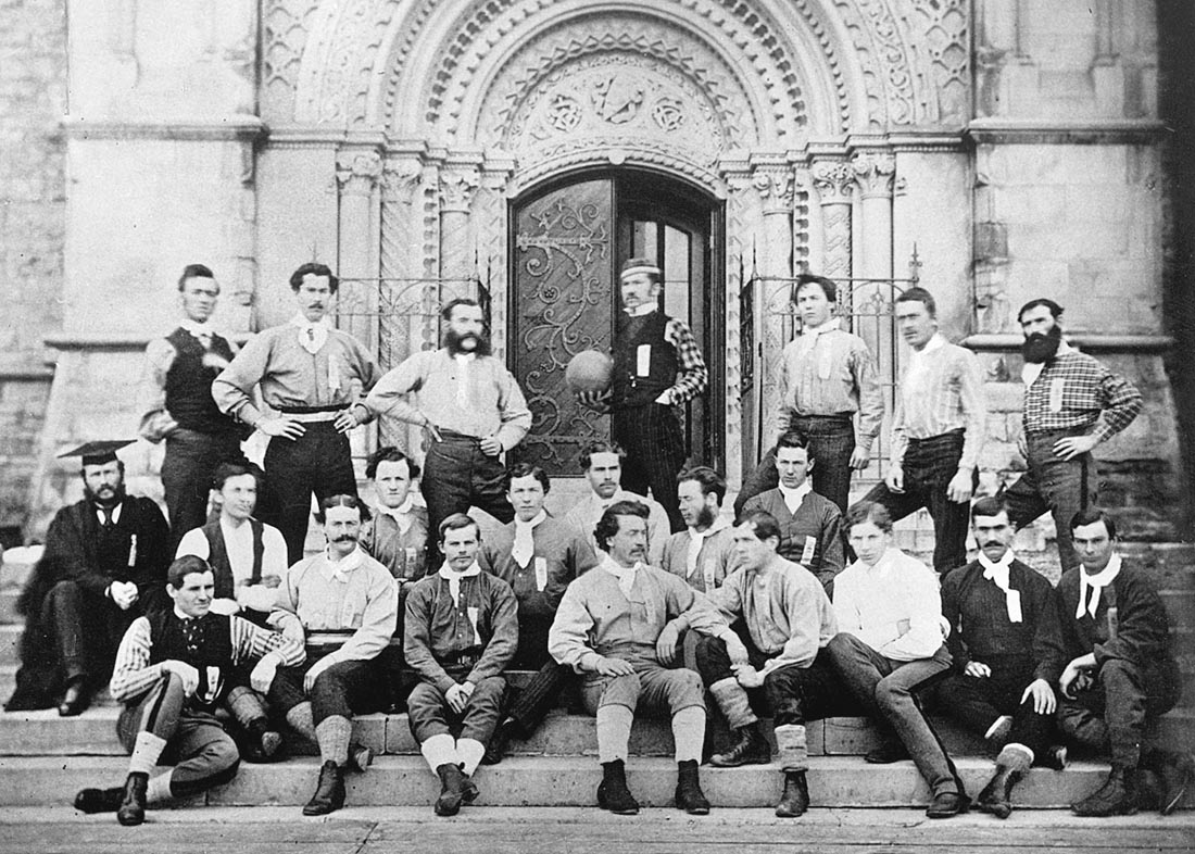 A group of men outside the front door of University College. In the centre, one holds a ball.