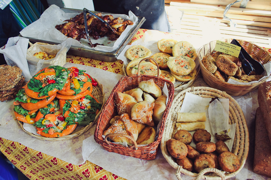 Baked goods for sale in baskets on a table including buns, flatbreads, and cookies.