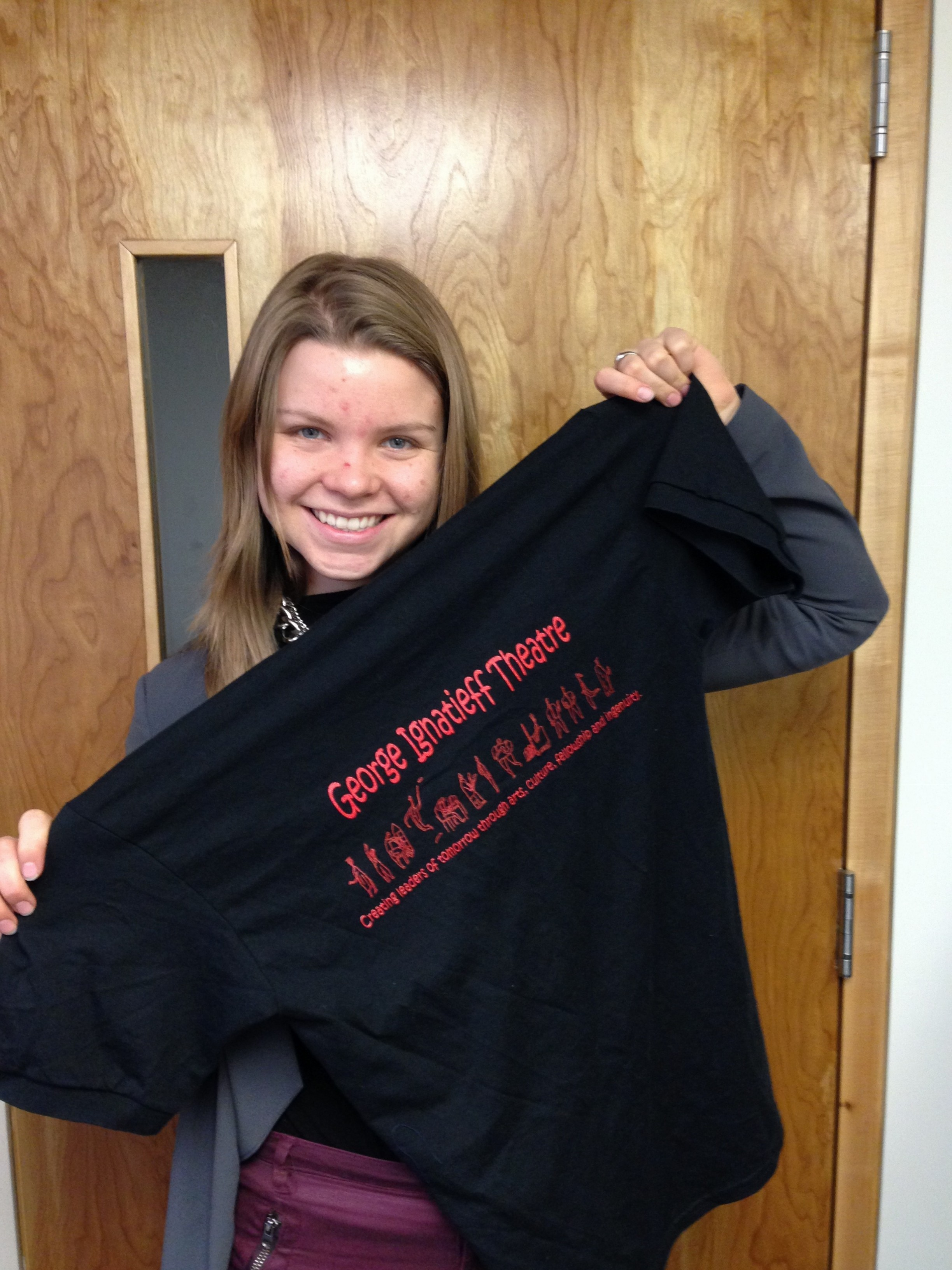 "Laura with her George Ignatieff Theatre t-shirt; the t-shirt says ""George Ignatieff Theatre: creating leaders of tomorrow through arts, culture, fellow, and ingenuity"" and shows drawings of people."