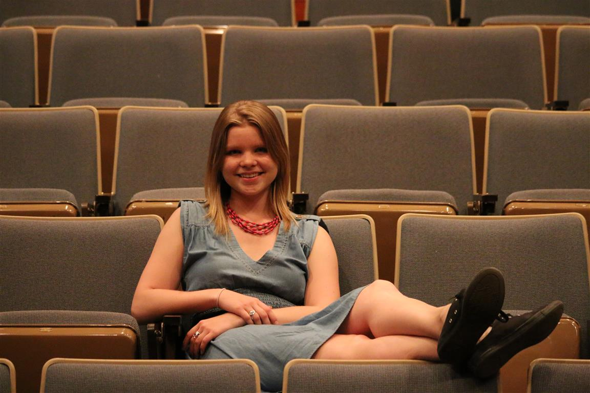 Laura with her feet up in the seats of the George Ignatieff Theatre.