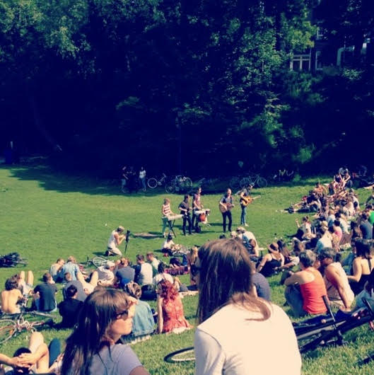 People sit in the dog bowl at Bellwoods watching a band at the music festival.
