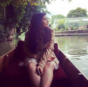 A picture of Sargam wearing a dress on a canoe, looking out into the distance with a contemplative look on her face