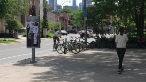 St. George Street, in front of the koffler centre, a lone biker and a bike rack