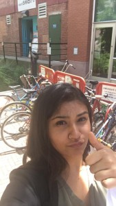 Sargam giving the camera a thumbs up with Bikechain's bike rack in the background