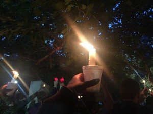 a picture of a lit candle being held during a vigil