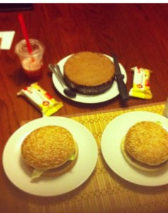 picture of two burgers, a cake and a smoothie all laid out in a fancy table arrangement