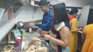 A picture of Sargam and her brother in front of a stack of roti