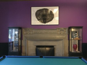 a photo of a contemporary painting hanging above a stone fireplace on a purple wall, beside the fireplace are two glass display cabinets with a dark wood frame and infront of the fireplace is a pool table