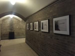 a photo of wall going down a hallway with 5 photographs in frames hanging along the wall. the wall is a grey brick.