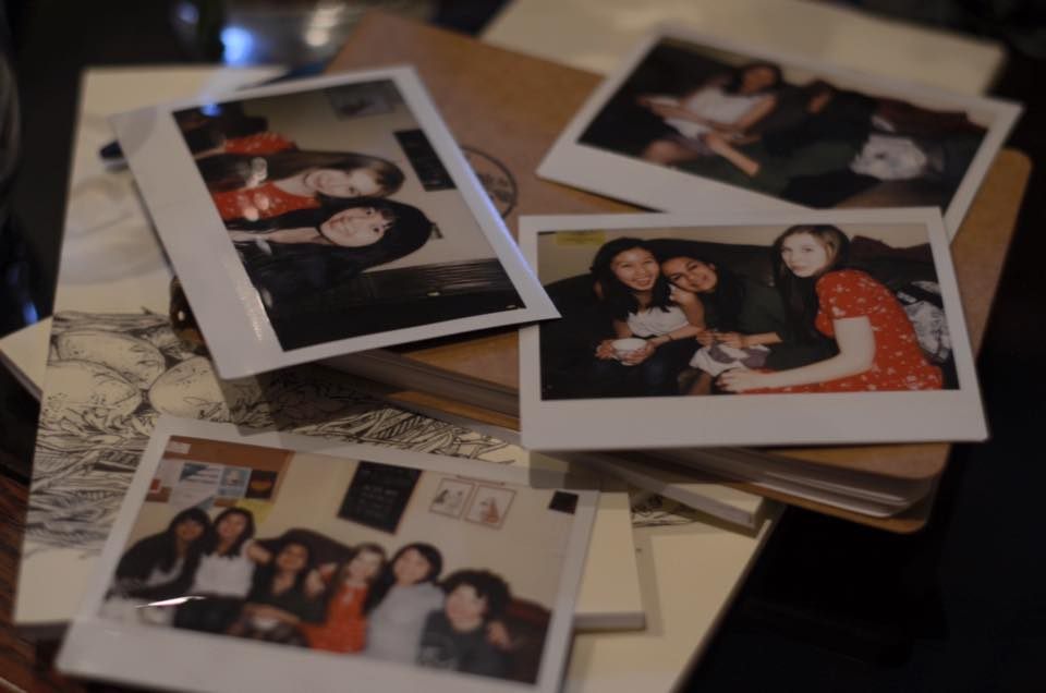 Polaroids on a table featuring Caffiends volunteers