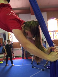 Annette is seen hanging upside down from a set of aerial silks.